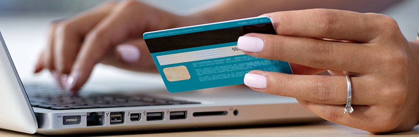 Using a laptop online shopping | holding a credit card