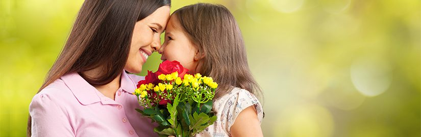 Image of a daughter and mother holding flowers and looking into each others eyes