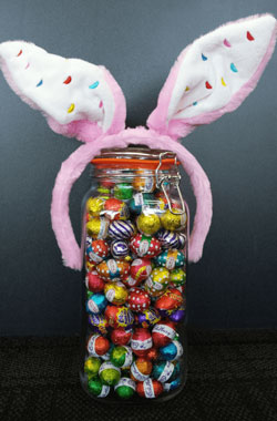 An image of a Jar filled with assorted chocolates for easter. On top of the jar there is an alice band that has bunny ears attached for Easter.
