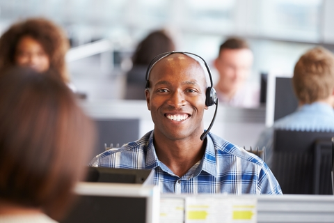African American man working in call centre, looks to camera.