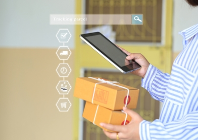 Man holding a tablet and product parcels, indicating delivery