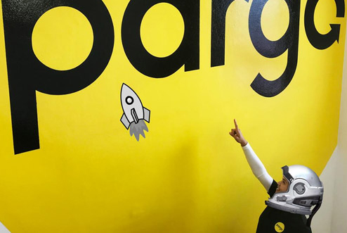 A kid pointing at a pargo logo