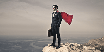 A business man wearing a cape and standing on a cliff