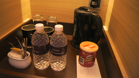 Image of a group of items, Image contains two bottles of water, pringle chips, cups and glasses